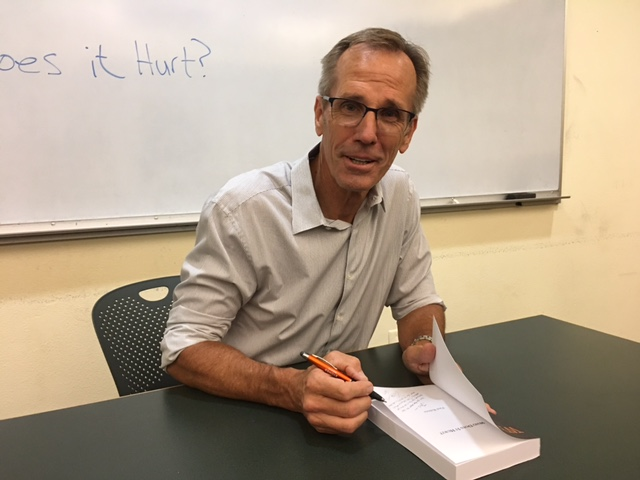 "Author Phil Robins signing copies of his new novel, ""Who Does It Hurt?"""